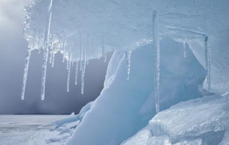 つらら: フォア グラウンド上のつららと冬の冷凍バイカル湖の屋外ビュー