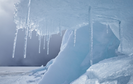 outdoor view of frozen baikal lake in winter with icicles on foreground