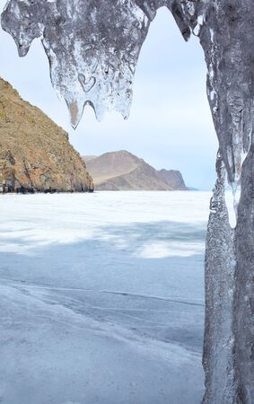 outdoor view of frozen baikal lake in winter with icicles on foreground photo