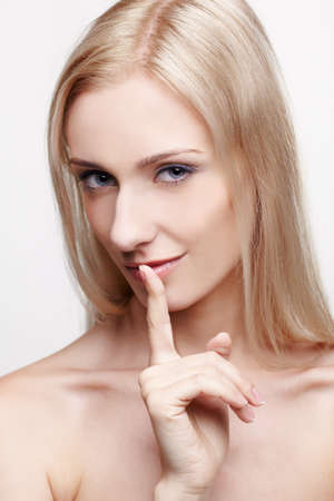 headshot portrait of young beautiful blonde woman asking to be quiet photo