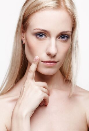 headshot portrait of young beautiful blonde woman placing finger on her cheek near leeps photo