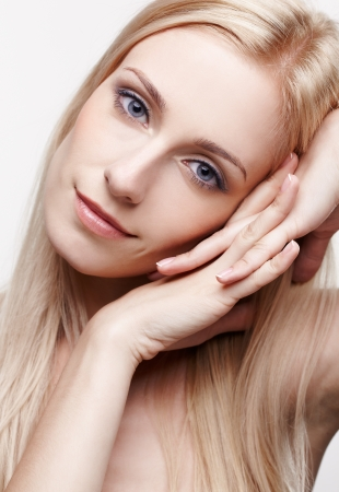 portrait of young beautiful blonde woman with healthy skin on gray photo