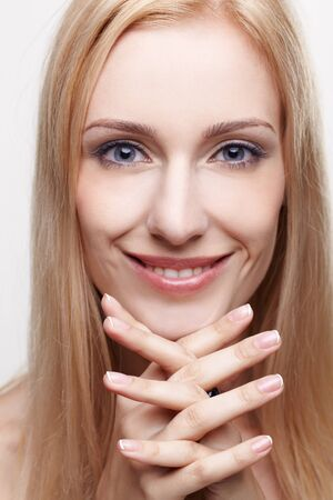 headshot portrait of young beautiful smiling blonde woman with manicured hands under chin photo