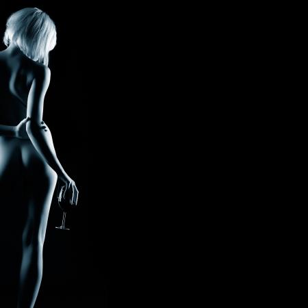 mujer rubia desnuda: retrato de joven mujer rubia desnuda con cuerpo hermoso posando con un vaso de vino tinto en la mano