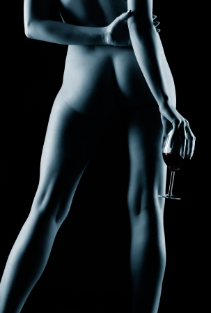 nude blonde woman: portrait of young nude blonde woman with beautiful buttocks and legs posing with glass of red wine in hand Stock Photo