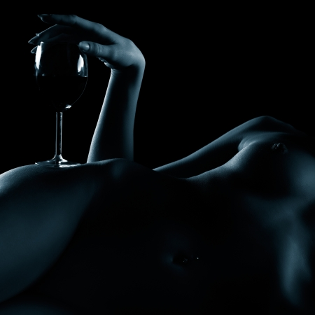 body part portrait of young nude woman with beautiful breasts with glass of red wine on her hip