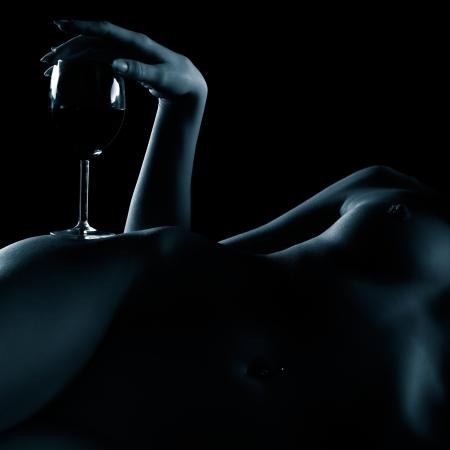 erotico: corpo ritratto parte di giovane donna nuda con il seno bello con vetro di vino rosso su un fianco Archivio Fotografico