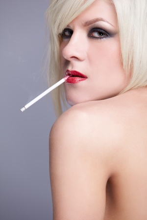 portrait of young topless blonde woman with beautiful body smoking slim cigarette photo