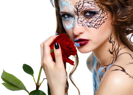 portrait of beautiful model with skew bodyart and hairdo posing with red rose photo