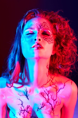 young naked girl: portrait of beautiful model with skew bodyart and hairdo in mixed red blue light