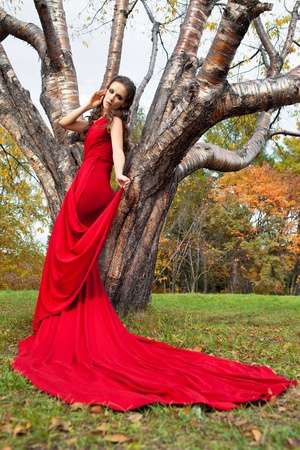 Woman in red dress walking in autumn park photo