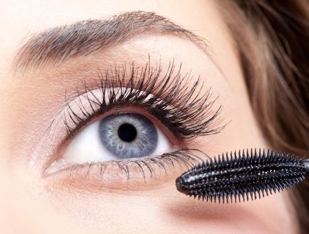 Młoda piękna kobieta stosowania makijażu tusz do rzęs na oczy pędzlem