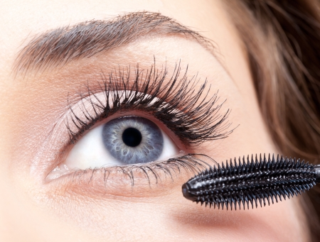 Young beautiful woman applying mascara makeup on eyes by brush Stock Photo - 16826536