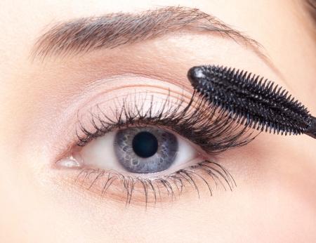 Joven y bella mujer de aplicar el maquillaje rimel en los ojos con pincel