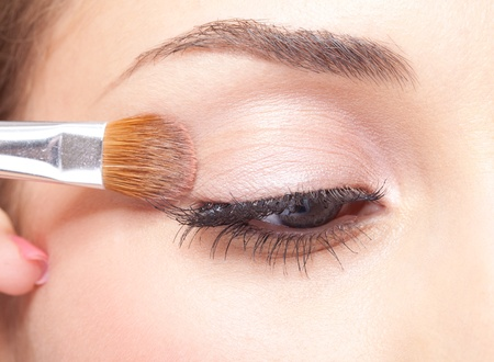 make up eyes: Young beautiful woman applying makeup eye shadows by brush Stock Photo