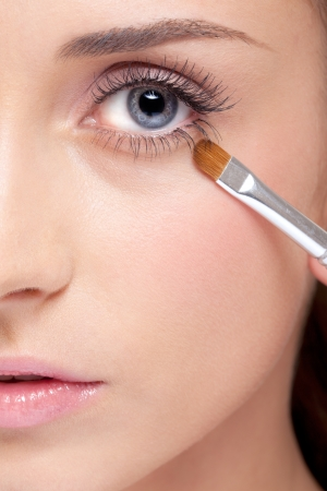 eye close up: Young beautiful woman applying makeup eye shadows by brush Stock Photo