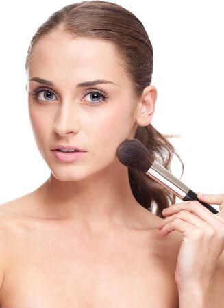 mujer maquillandose: Joven y bella mujer de aplicar el maquillaje en la cara con una brocha