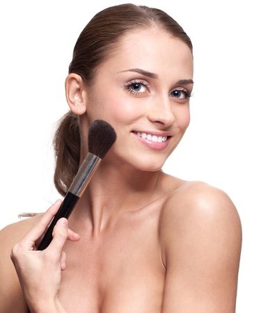 Happy young beautiful woman applying makeup on face by brush photo