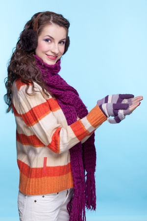 Young pretty woman in winter dress on blue background Stock Photo - 17098927