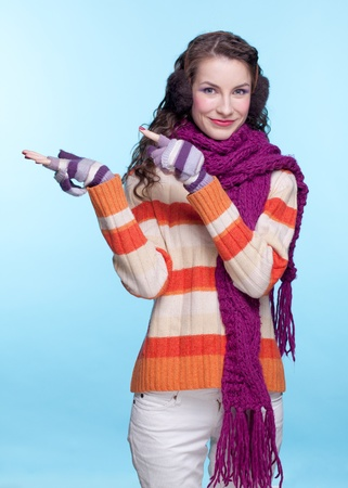 Young pretty woman in winter dress on blue background Stock Photo - 17098932