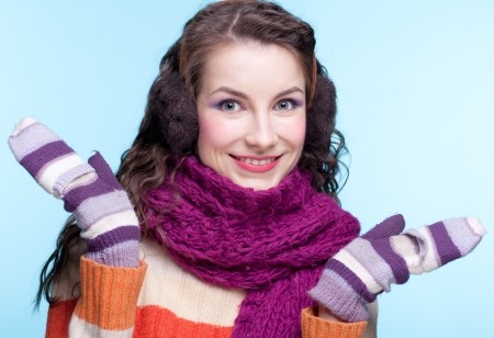 earmuffs: Young pretty woman in winter dress on blue background