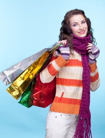 Young pretty woman in winter dress on blue background with shopping bags photo