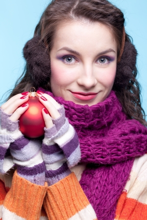 earmuffs: Young pretty woman in winter dress on blue background with Christmas ball in hands Stock Photo