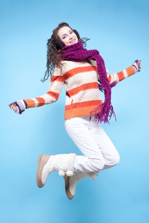 Young pretty woman in winter dress jumping on blue background Stock Photo - 17098954