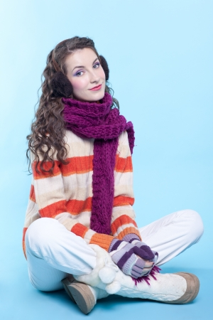 Young pretty woman in winter dress sitting on blue background Stock Photo - 17098951