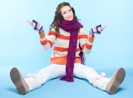 Young pretty woman in winter dress sitting on blue background Stock Photo - 17098955