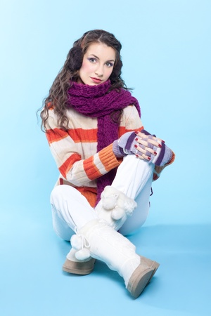 Young pretty woman in winter dress sitting on blue background photo