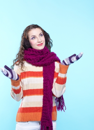 Young pretty woman in winter dress on blue background photo