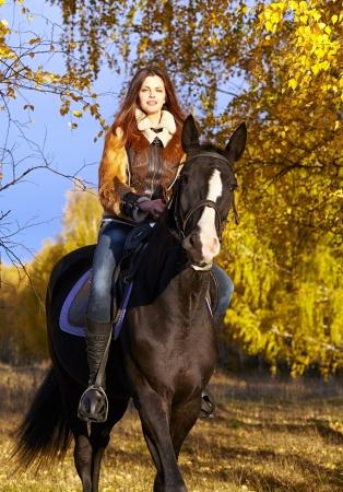 caballo negro: Retrato de una mujer muy joven con un caballo negro cabalgando d�a de oto�o
