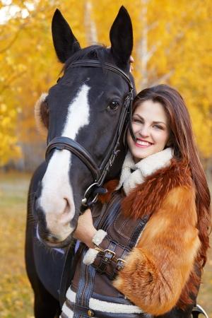 jinete: Retrato de una mujer muy joven con un caballo negro caballo día de otoño