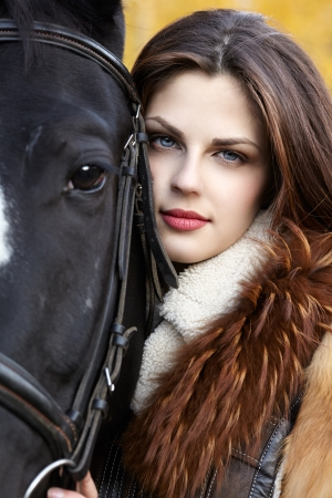Portrait of a pretty young woman with a black horse riding autumn day