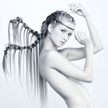 Young woman with creative hair style and plaits photo