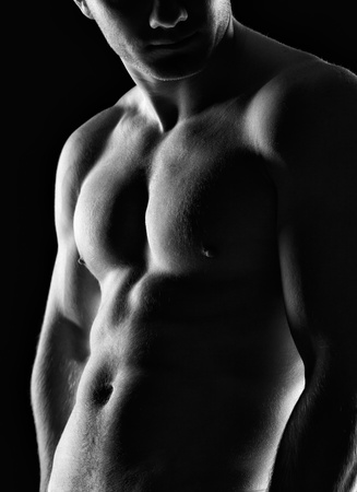 Silhouette of young athlete bodybuilder man on black