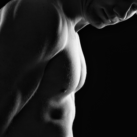 naked body: Silhouette of young athlete bodybuilder man on black