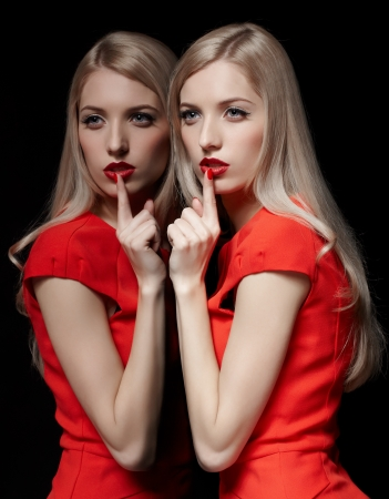 portrait of young beautiful blonde woman in red dress at mirror asking to be quiet Stock Photo - 17566688