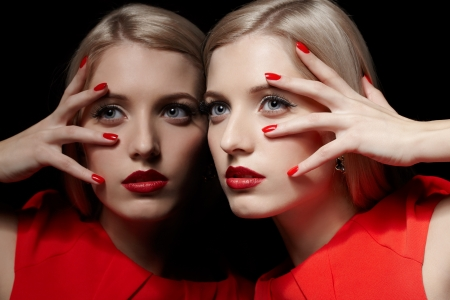 portrait of young beautiful long-haired blonde woman in red dress leaning at  mirror and touching her face with red manicured fingers photo