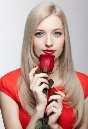 portrait of young beautiful blonde woman in red dress with red rose flower in hands Stock Photo - 17566739