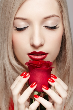 portrait of young beautiful blonde woman closing eyes and holding red rose flower in manicured hands photo