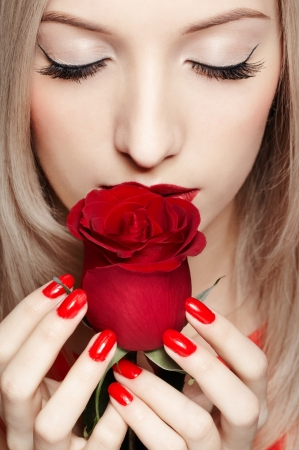 portrait of young beautiful blonde woman closing eyes and holding red rose in manicured hands Stock Photo - 17566759