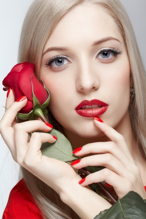 portrait of young beautiful blonde woman with red rose in manicured hands photo