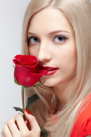 portrait of young beautiful blonde woman with red rose flower in manicured hand photo