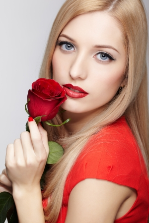 portrait of young beautiful blonde woman in red dress with red rose flower in hands photo