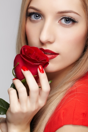 portrait of young beautiful blonde woman in red dress with red rose in hands photo