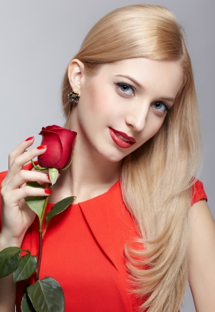 portrait of young beautiful blonde woman in red dress with red rose in hand