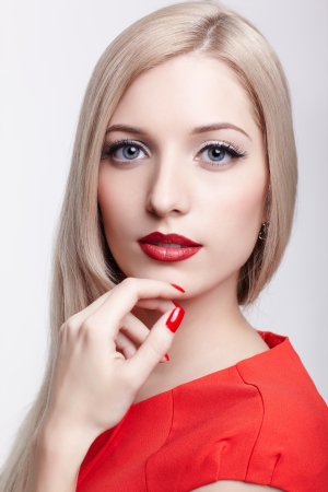 portrait of young beautiful blonde woman in red dress with red manicred fingers photo