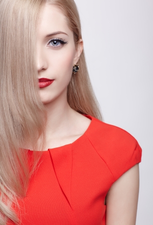 portrait of young beautiful blonde woman in red dress with half of face behind long hair Stock Photo